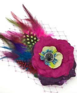 Front side of a hot pink feather hair clip fascinator against a white background