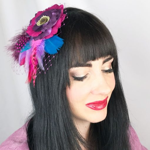 A close up of a woman wearing a violet purple hot pink feather hair clip fascinator in her hair