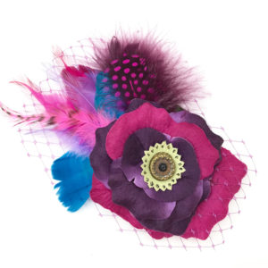 Front side of a violet purple hot pink feather hair clip fascinator against a white background