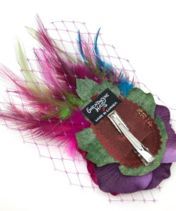 Back side of a hot pink feather hair clip fascinator against a white background