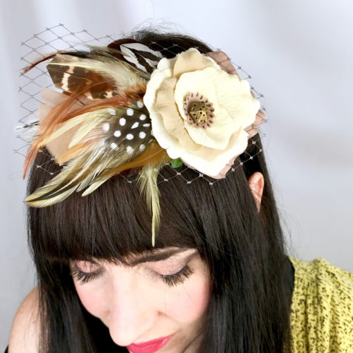 A close up of a woman wearing a ivory and tan rose and feather hair clip fascinator in her hair