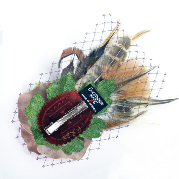 the backside of an ivory tan rose and feather hair clip fascinator against a white background