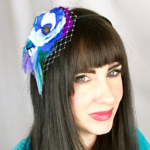 A close up of a woman wearing a light blue feather hair clip fascinator in her hair