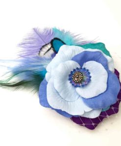 Front side of a light blue feather hair clip fascinator against a white background