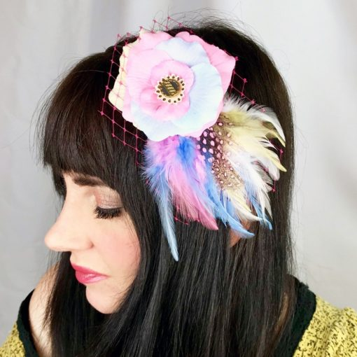 A close up of a woman wearing a pastel pink light rose flower ivory feather hair clip fascinator in her hair