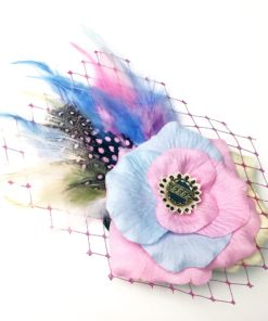 Front side of a pastel pink light rose flower ivory feather hair clip fascinator against a white background