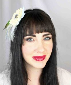 A close up of a woman wearing a pale yellow rose white feather hair clip fascinator in her hair