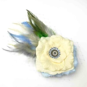 Front side of a pale yellow rose white feather hair clip fascinator against a white background