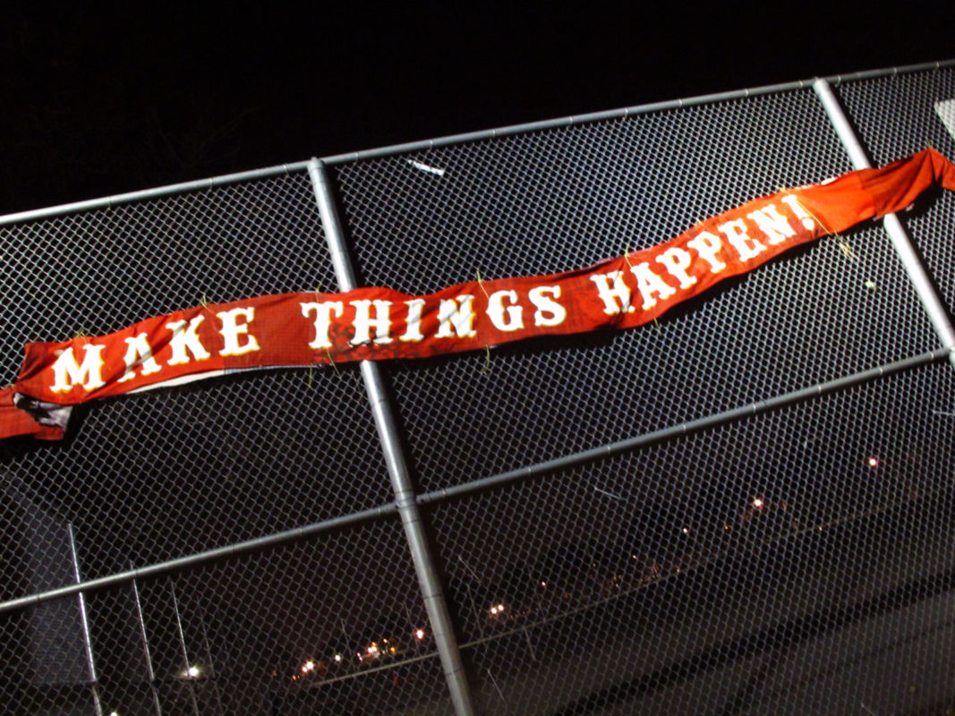 A red banner with the words Make things Happen in white block letters attached to a tennis fence photo shot in the night