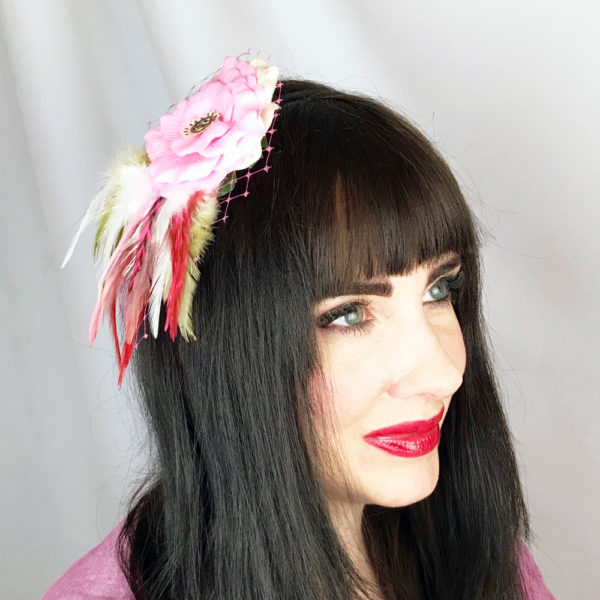 A close up of a woman wearing a pink candy rose white feather hair clip fascinator in her hair