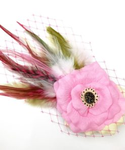 Front side of a pink candy rose white feather hair clip fascinator against a white background