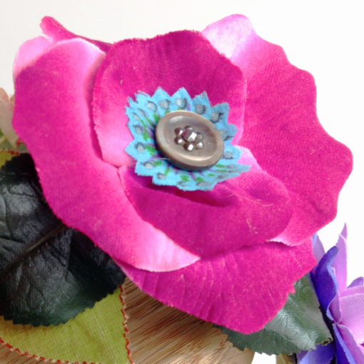 A close up of the pink rose and antique button against a white background