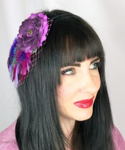 A close up of a woman wearing a violet purple feather hair clip fascinator in her hair