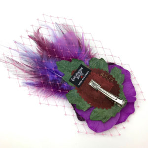 Back side of a violet purple feather hair clip fascinator against a white background