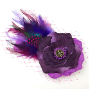 Front side of a violet purple feather hair clip fascinator against a white background