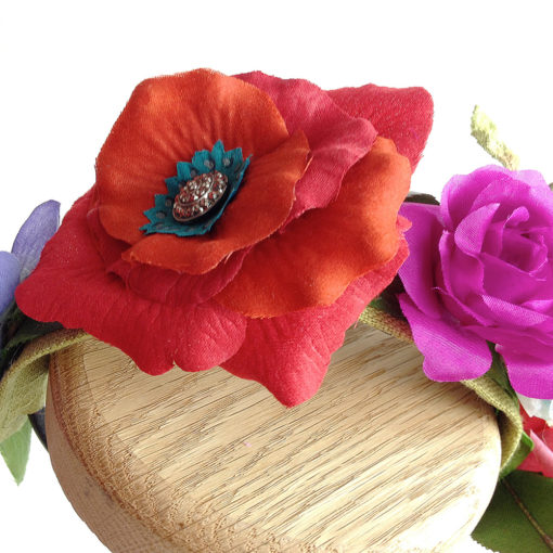 A close up of the red rose and antique button against a white background