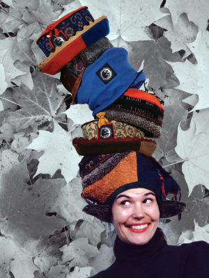 Gwendolyne smiling with 6 of her hat designs on her head.