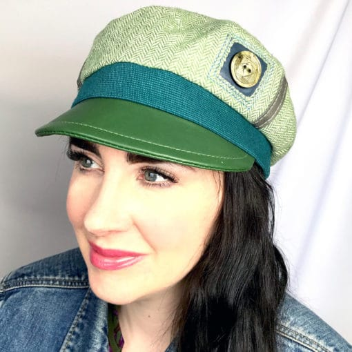 A close up of a woman wearing a Green herring bone Abbey Road Cap