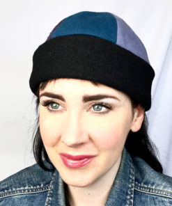 A close up of a woman wearing a blue and black Bean toque