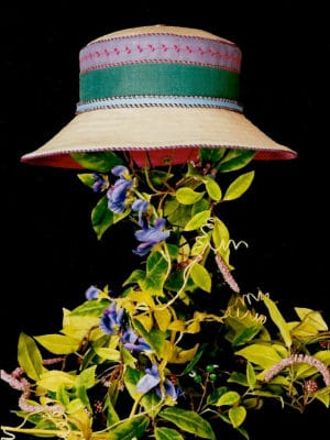 A blue and green summer wide rim Degas linen summer hat on a stand covered with leaves set against a black background