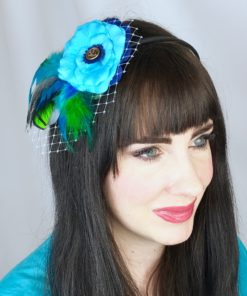 A close up of a woman wearing a turquoise blue rose flower green feather hair clip fascinator in her hair