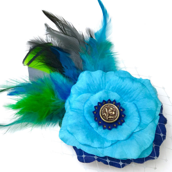 Front side of a turquoise blue rose flower green feather hair clip fascinator against a white background