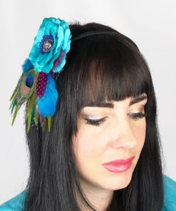 A close up of a woman wearing a turquoise rose and peacock feather hair clip fascinator in her hair