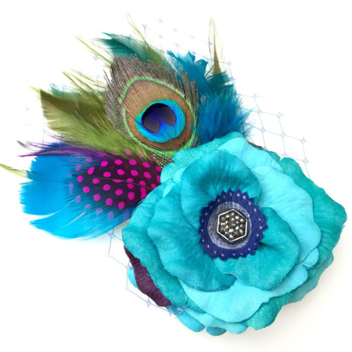Front side of a turquoise rose and peacock feather hair clip fascinator against a white background
