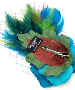 Back side of a turquoise rose and peacock feather hair clip fascinator against a white background