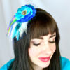 Woman wearing a turquoise and royal blue rose and feather hair clip fascinator in her hair