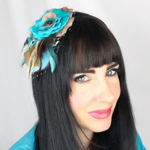 A close up of a woman wearing a turquoise blue tan rose feather hair clip fascinator in her hair
