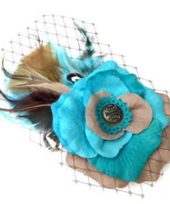 Front side of a turquoise blue tan feather hair clip fascinator against a white background