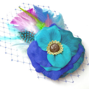 Front side of a turquoise blue white feather hair clip fascinator against a white background