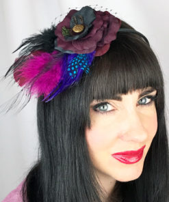 A close up of a woman wearing a black and wine rose and feather hair clip fascinator in her hair