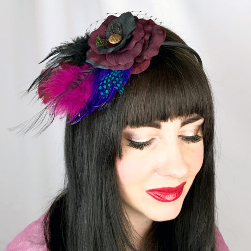A close up of a woman wearing a wine and black rose and feather hair clip fascinator in her hair