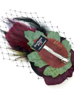 Back side of a wine and black rose and feather hair clip fascinator against a white background