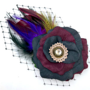 Front side of a wine and black feather hair clip fascinator against a white background