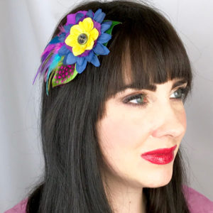 A close up of a woman wearing a yellow and navy blue small flower feather hair clip fascinator in her hair