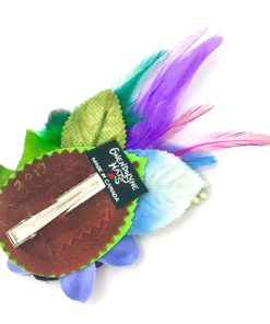 The back side of a custom Gwendolyne Hats handmade flower hair clip fascinator with an antique button, leaf, and feathers.