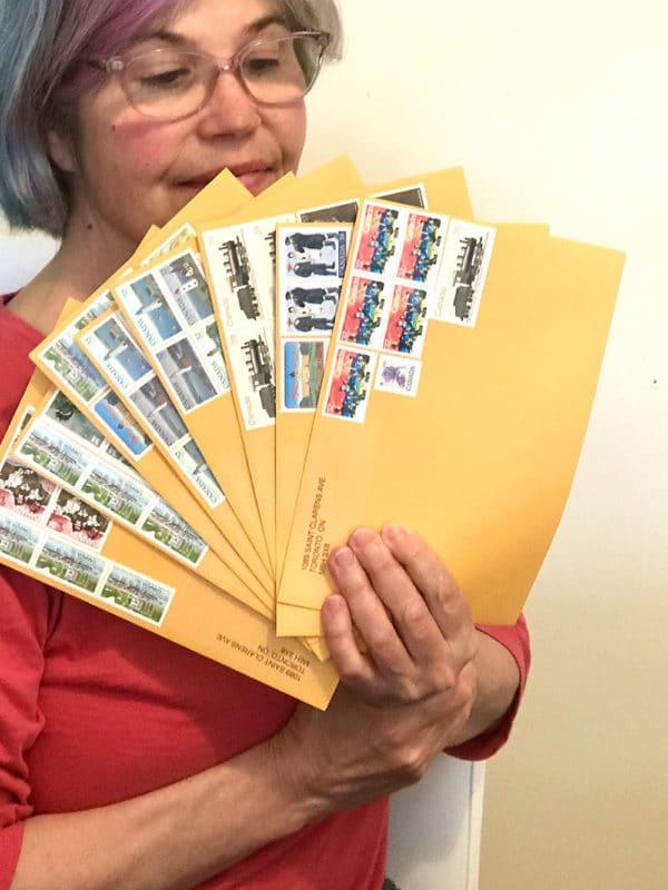 Gwendolyne holding up envelopes with vintage postage stamps