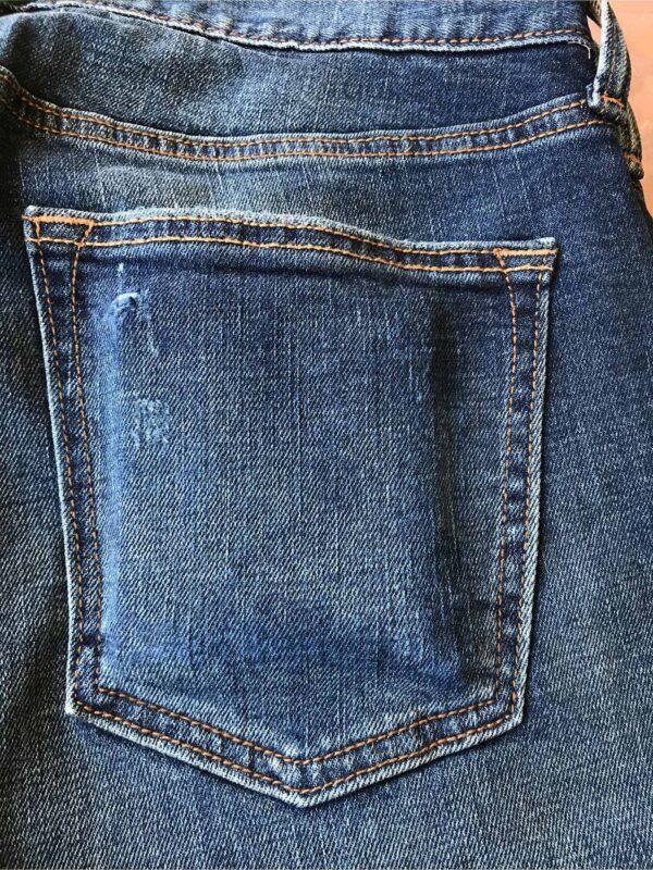 Aged detail of back jean pocket