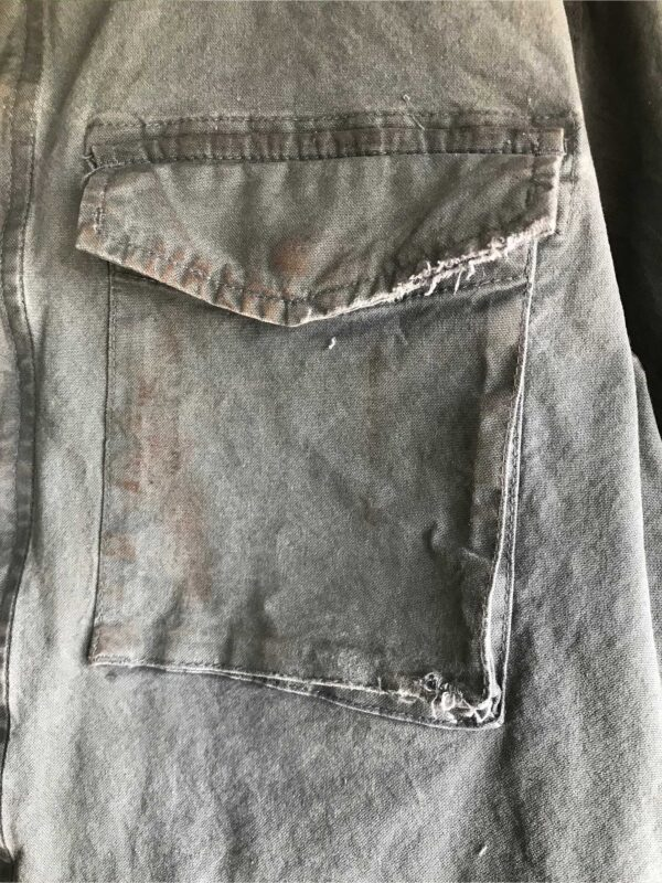 Aged detail of green jacket snap flap pocket